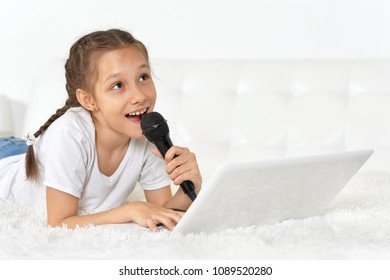 portrait of a little girl lying on the bed with a laptop and a microphone