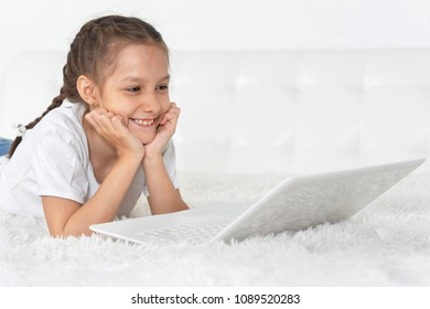 portrait of a little girl lying on the bed with a laptop