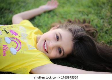 Porträt eines kleinen Mädchens, das auf einem Gras liegt. Mutterschaft, Kindergarten, Kinderkonzept
