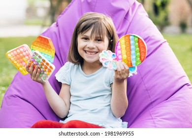 Portrait little girl with a modern popit toy. Colorful and bright pop it toy. Simple dimple. The child is sitting on a easy chair with colorful trendy antistress sensory toy pop it and simple dimple