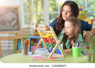 Portrait of little girl with mother using abacus