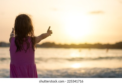 Portrait of little girl on the beach. Back view.