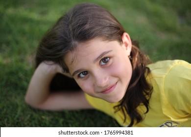 Porträt eines kleinen Mädchens auf unscharfem grünem Hintergrund. Mutterschaft, Kindergarten, Kinderkonzept