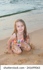 Portrait of a little girl on the shore of the evening sea