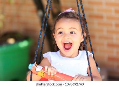 Portrait of a little girl on a swing