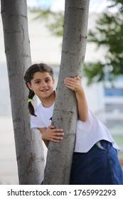 Porträt eines kleinen Mädchens auf einem Baum. Mutterschaft, Kindergarten, Kinderkonzept