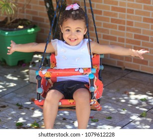 Portrait of a little girl with open arms on a swing