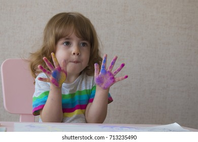 Portrait of a little girl with painted palms. The girl is sitting on a chair at the table