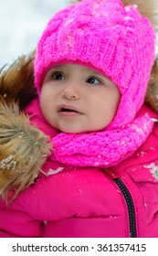 Portrait of a little girl in a pink hat during a snow walk