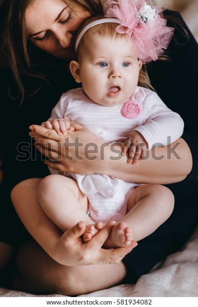 Portrait of a little girl with a pink headband. on the mother's hands