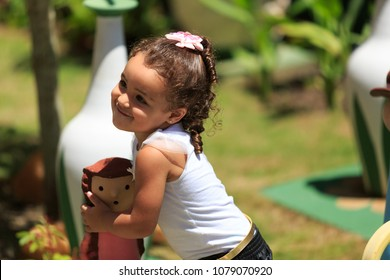 Portrait of a little girl playing with a clay doll