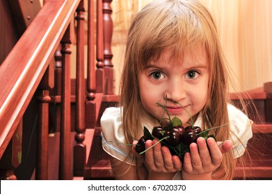 Portrait of little girl playing in home on stairs with plastic cherry berry
