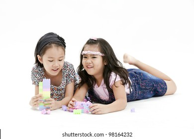 portrait of a little girl playing puzzle with each other