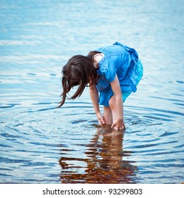 Portrait of a little girl playing in water