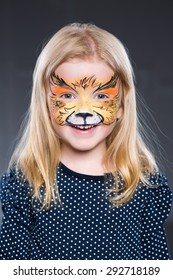 Portrait of little girl posing with the face painted like cat