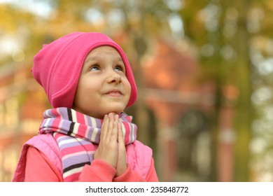 Portrait of a little Girl prays autumn park