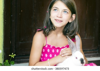 Portrait of a little girl with rabbit on her lap