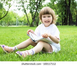 Portrait of little girl reading a book in the summer park
