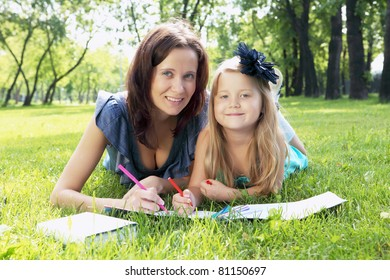 Portrait of little girl reading a book in the park with her mother