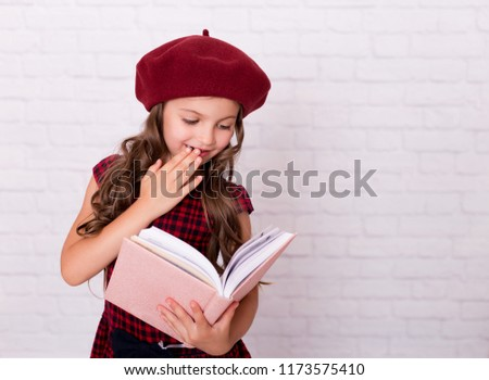 Portrait of a little girl in a red beret holding open pink notebook.  Childhood. 2011901f8ba
