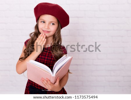 Portrait of a little girl in a red beret holding open pink notebook. Back to 8a4a7e9fc57