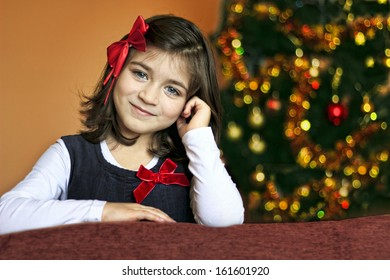 Portrait of a little girl with a red ribbon in front of Christmas tree