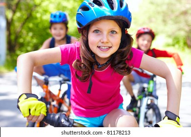 Portrait of a little girl riding her bike ahead of her friends