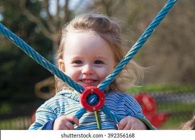 Portrait of a little girl with a rope in his hand on the playground