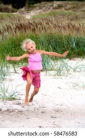 Portrait of the little girl running on a beach