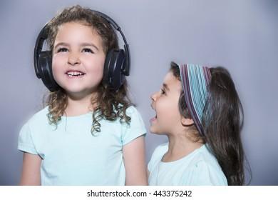 Portrait of little girl screaming at her older sister listening to music in headphones