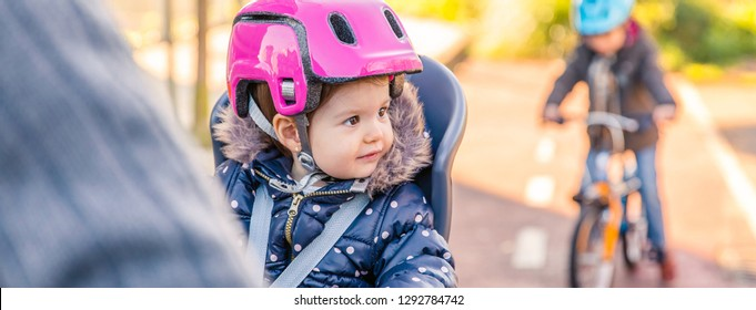 Portrait of little girl with security helmet on the head sitting in bike seat and her brother with bicycle on the background. Safe and child protection concept.