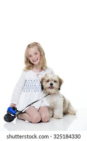 Portrait of a little girl sitting down with her dog. She is looking at the camera and smiling.