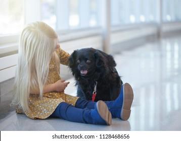 Portrait of little girl sitting on floor and stroking black dog