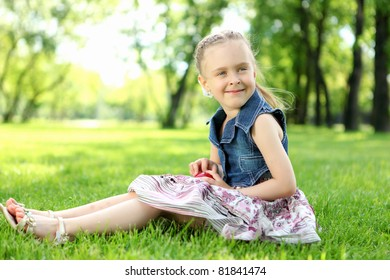 Portrait of a little girl sitting on the grass  in the park