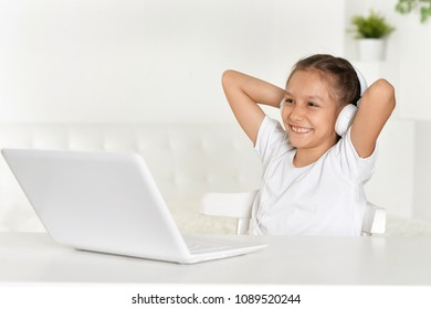 portrait of little girl sitting at table with laptop and listening to music