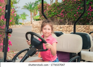 Portrait of a little girl sitting at the wheel of a golf cart. A child is playing a driver sitting on an electric car. Little tourist has fun at a tropical resort