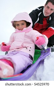 Portrait of a little girl sledding next to a man
