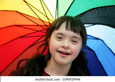 Portrait of little girl smiling on background of the colorful umbrella