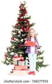 Portrait of little girl standing near Christmas tree with letter to Santa in her hands on white background