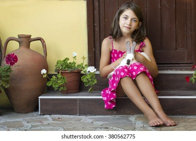 Portrait of a little girl standing on the stairs with rabbit on her lap