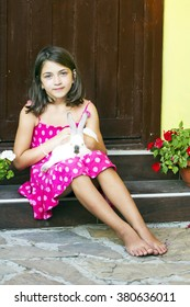 Portrait of a little girl standing on the stairs with rabbit on