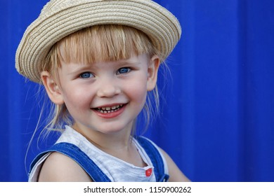 Portrait of a little girl in a straw hat. She looks at the viewer and smiles at the camera.