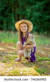 Portrait of a little girl in a straw hat with Teddy bear in hand, a summer day, greenery around