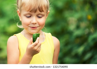 Portrait of a little girl surprised looking at a cucumber