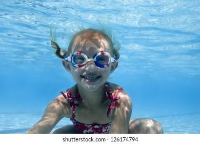 Portrait of little girl swimming underwater