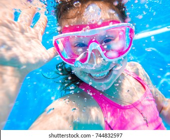 Portrait of little girl swimming underwater in pool. Cute  girl  in mask creates bubbles under water