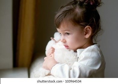 Portrait of little girl with teddy bear looking through a window