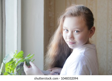 Portrait of a little girl teenager watering flowers at home