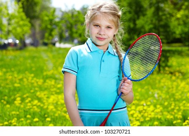 Portrait of little girl with tennis racket looking at camera