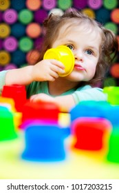 Portrait of a little girl with two tails that plays with colorful plastic cups. The girl brought the yellow glass to her mouth and pondered